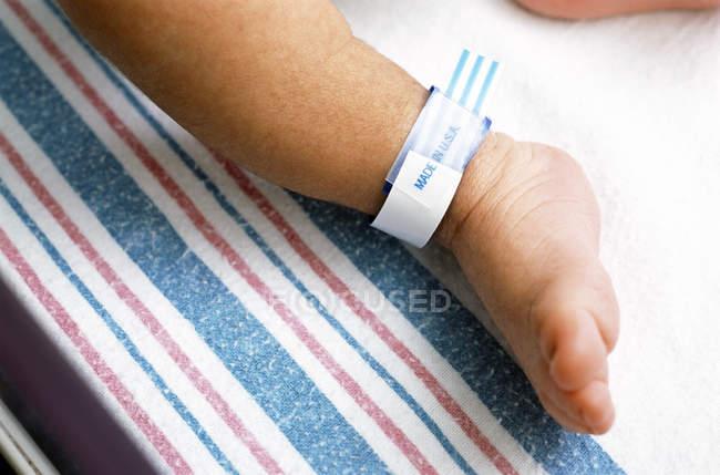 Close Up Of Hospital Identification Bracelet On Newborn Boy Ankle Stock Photo
