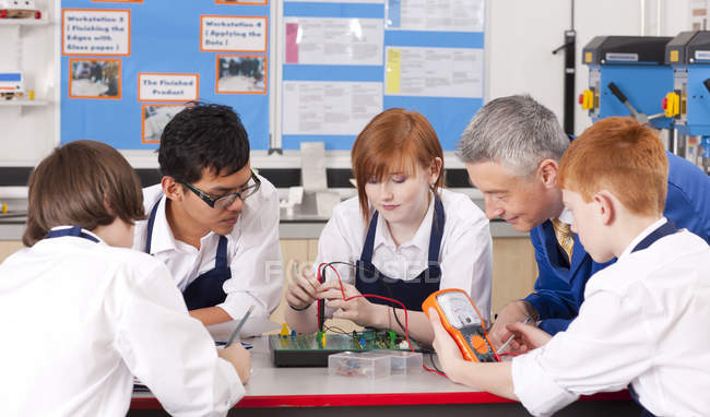 Side view of teacher watching group of students using electronic measuring device at table in vocational class — Stock Photo
