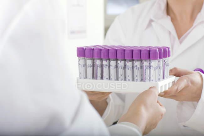 Technician handing vials to co-worker in laboratory — Stock Photo