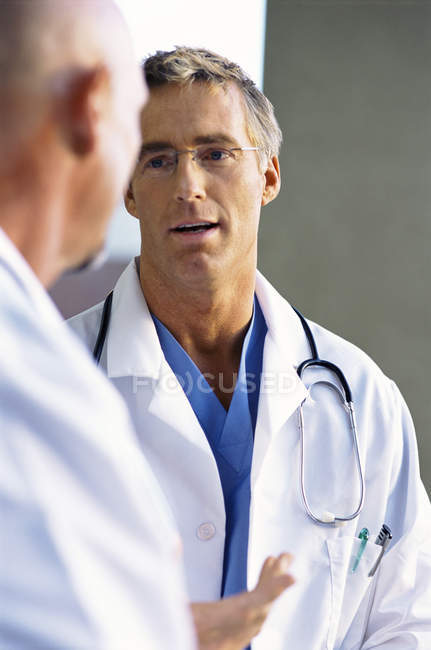 Doctors in lab coats talking face to face — Stock Photo