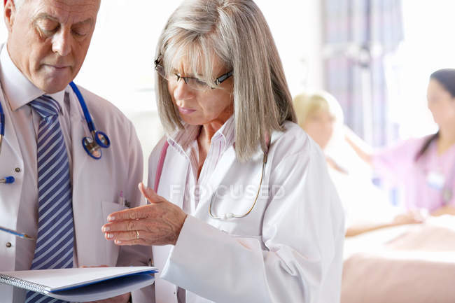 Doctors discussing medical chart in hospital with patient and nurse in background — Stock Photo
