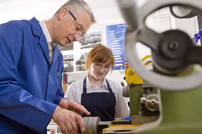 Side view of teacher explaining to student how to use lathe in metalwork class — Stock Photo