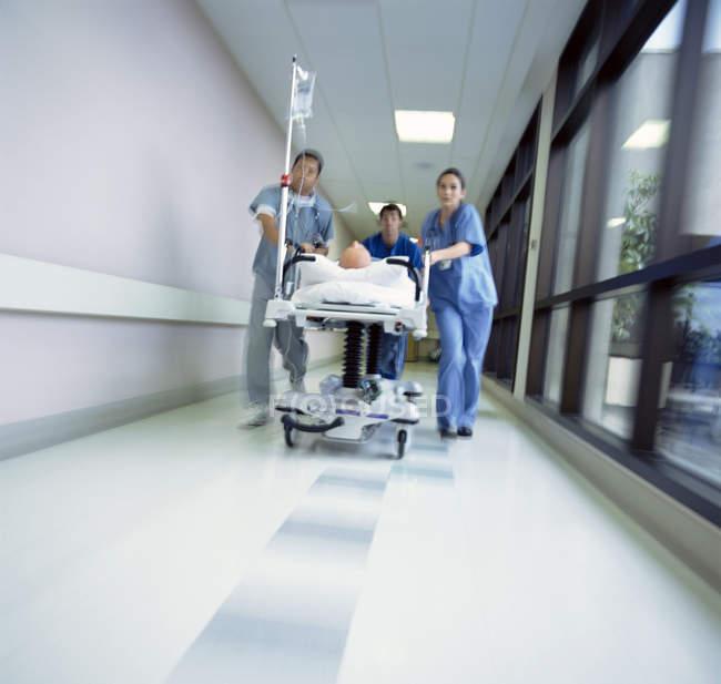 Medici, correndo con il paziente sulla barella dell'ospedale attraverso corridoio — Foto stock