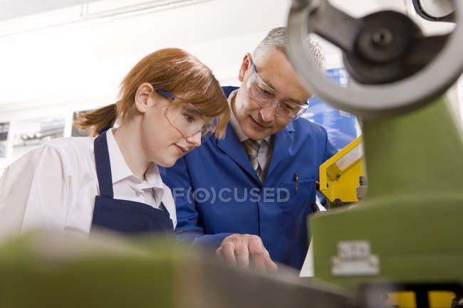 Low angle view of teacher explaining to female student how to use lathe in metalwork class — Stock Photo