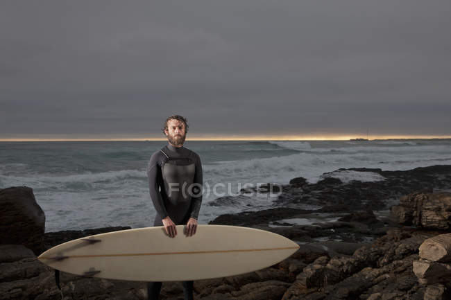 Surfer with surfboard standing on rocks wearing wetsuit with ocean in background and dramatic mood sky — Stock Photo