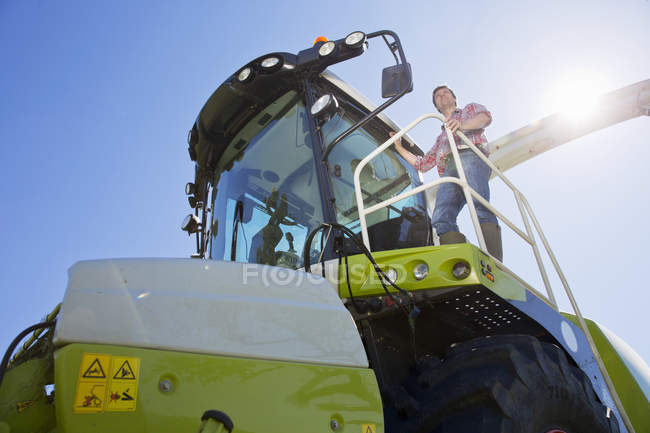 Farmer climbing into forage harvester with tractor in background — Stock Photo