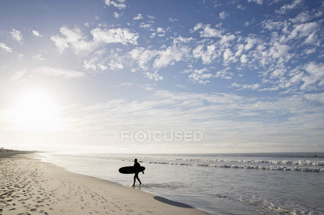 Ocean and surfers on sandy beach — Stock Photo