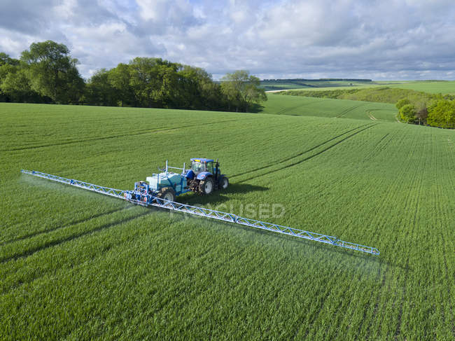 Aerial view of tractor spraying crop in green farm fields with pesticide — Stock Photo