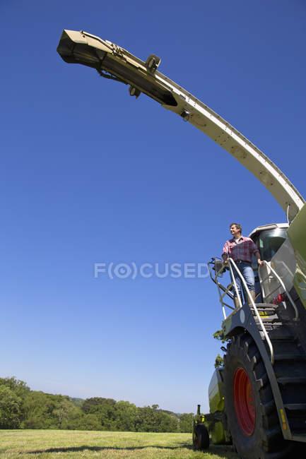 Фермер, глядя на урожай поле время стоя на корма комбайн шаги — стоковое фото