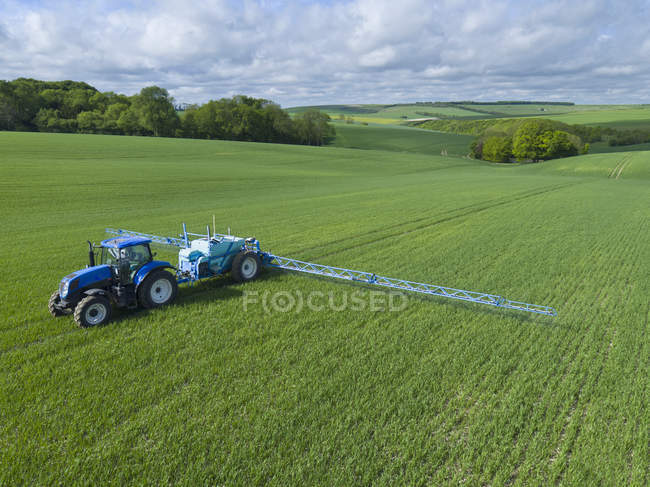 Tractor spraying crop in green farm fields with pesticide — Stock Photo