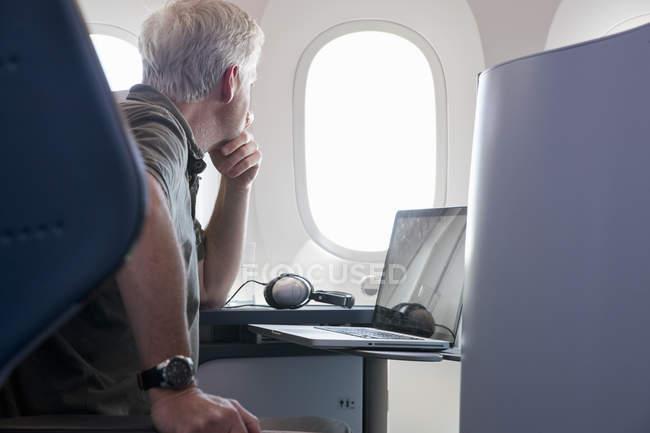 Pasajero busca por ventana de avión durante el vuelo con el portátil - foto de stock