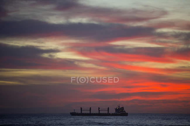 Cargo ship on ocean at sunset — Stock Photo