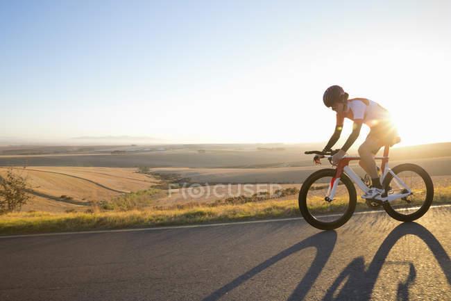 Weibliche Radfahrer Reiten Rennen Fahrrad auf sonniger Straße — Stockfoto