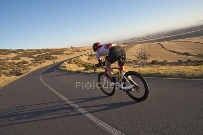 Vélo course cycliste féminine sur route ouverte ensoleillée — Photo de stock