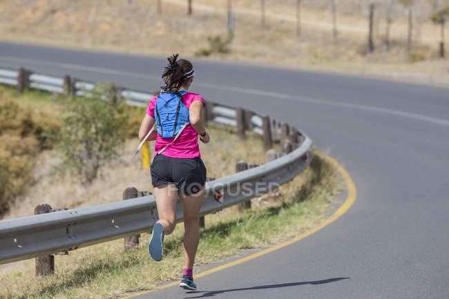 Female runner running on open road in arid landscape — Stock Photo