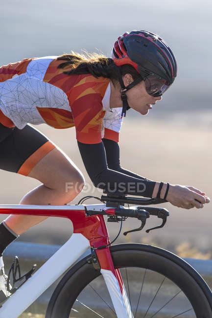 Nahaufnahme des weiblichen Radfahrer Reiten Rennen Fahrrad auf sonniger Straße — Stockfoto