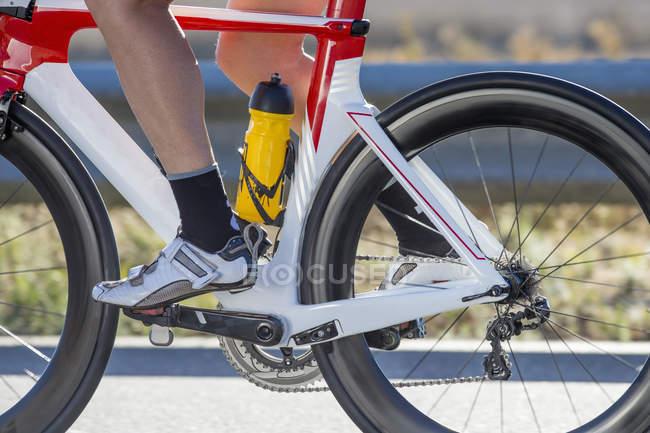 Gros plan du cycliste féminine le pied sur la pédale de vélo de course — Photo de stock
