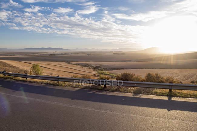 Vista da estrada aberta ao nascer do sol na paisagem árida — Fotografia de Stock