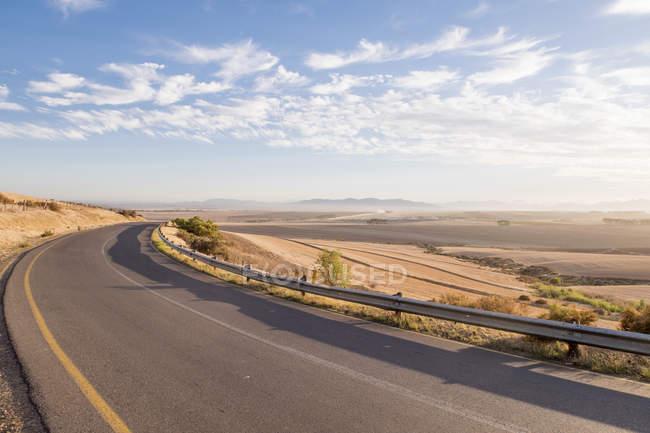 Vista da estrada longa aberta ao nascer do sol na paisagem árida — Fotografia de Stock