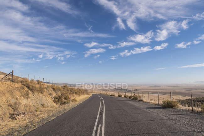 Blick auf lange Landstraße bei Sonnenaufgang in ariden Landschaft — Stockfoto