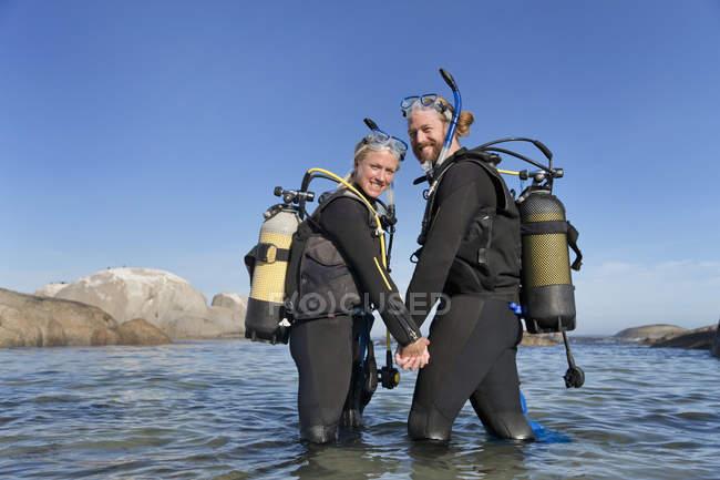 Couple souriant à la caméra et va de plongée en néoprène de la plage rocheuse de l'océan — Photo de stock