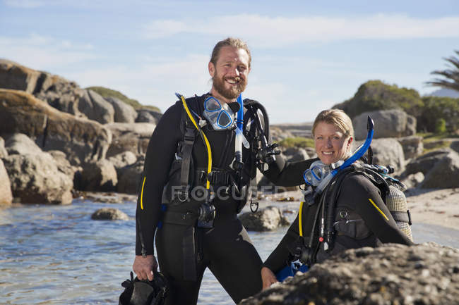 Couple in wetsuits going ocean scuba diving from rocky beach and smiling at camera — Stock Photo
