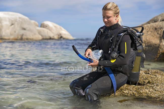 Жіноча Дайвер очищення маску до океану підводного плавання від пляжу — стокове фото