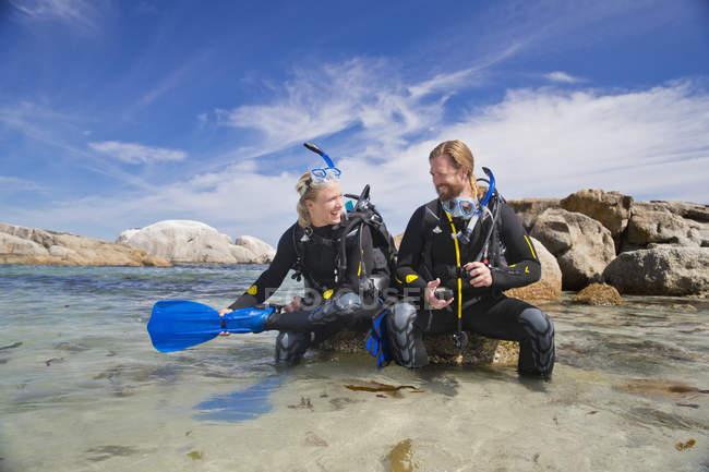 Couple en néoprène allant plongée océan plage rocheuse et souriant à l'autre — Photo de stock