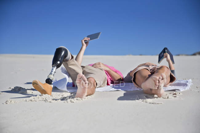 Man With Artificial Leg Lying On Sand And Looking At Digital Tablet With Female Partner On Beach Vacation — Stock Photo