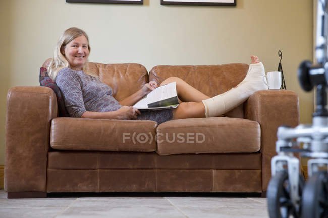 Portrait Of Mature Woman With Leg In Plaster Cast Lying On Sofa At Home — Stock Photo