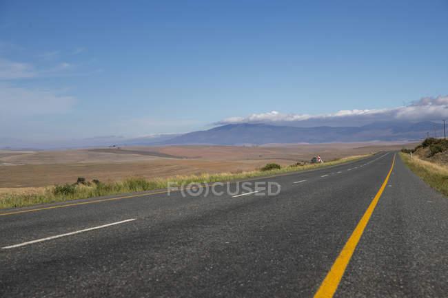 Estrada reta do país levando pela paisagem árida de África do Sul — Fotografia de Stock