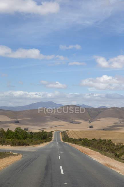 Estrada reta, atravessa a árida paisagem agrícola na região do cabo ocidental da África do Sul — Fotografia de Stock