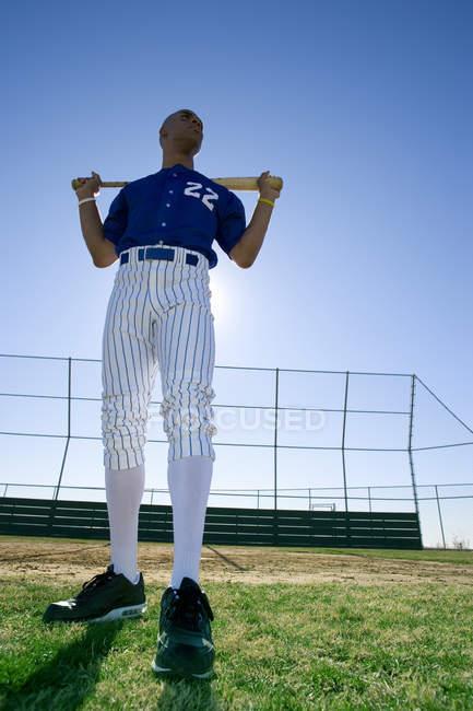 Pâte de base-ball en bleu uniforme debout sur terrain avec bâton sur l'épaule — Photo de stock