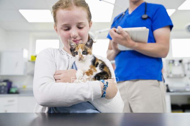 Veterinario con gato del gatito del animal doméstico en cirugía por mesa con el dueño del niño mirando a cámara - foto de stock