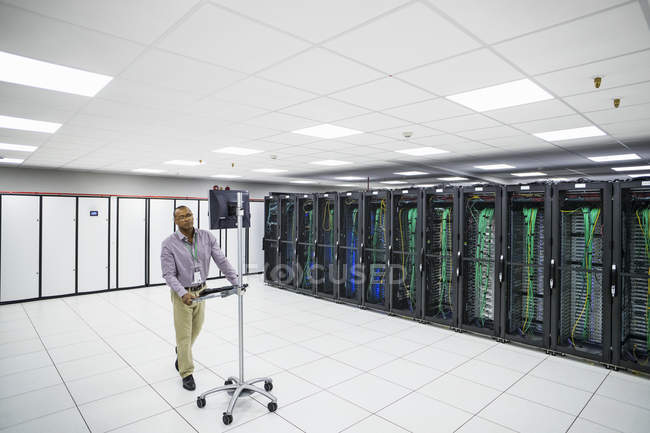 Technician working with mainframe computers in data center server farm — Stock Photo