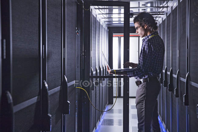 Technician with laptop working at mainframe computers in data center server farm — Stock Photo