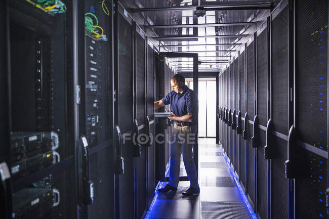 Technician fitting switch at mainframe computers in data center server farm — Stock Photo