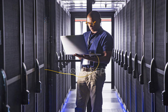 Техник с ноутбук работает на ЭВМ в ферме серверов центра данных — стоковое фото