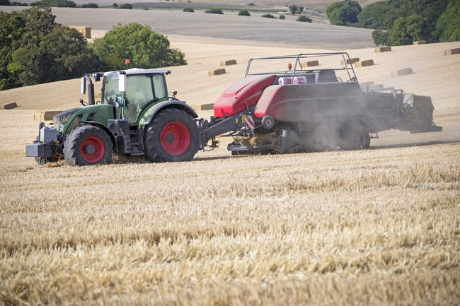 Tractor baler making straw bales in field after summer wheat harvest on farm — Stock Photo