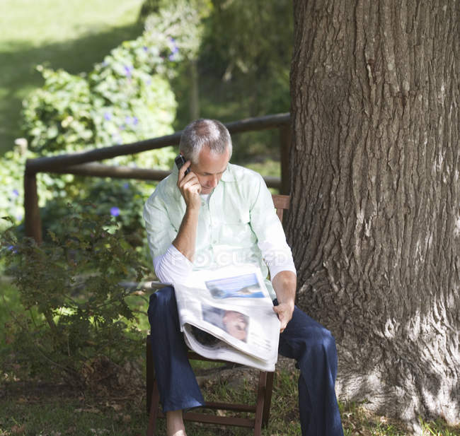 Man with a newspaper and mobile phone sitting next to a tree — Stock Photo