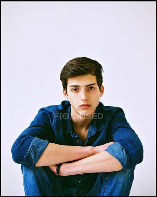Homme chemise jeans assis sur les genoux — Photo de stock
