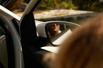 Reflet de la jeune fille blonde dans rétroviseur — Photo de stock