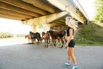 Жінка дивиться коней по дорозі в сільській місцевості — стокове фото