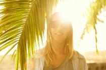 Woman posing on beach with palm tree — Stock Photo