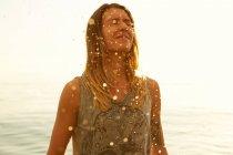 Жінка в м'яким сонячним промінням на пляжі — стокове фото