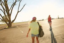 Женщины, езда на скейтборде с Рюкзаки — стоковое фото