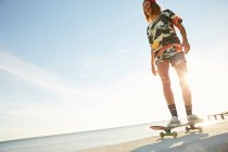 Woman standing with skateboard on seaside — Stock Photo