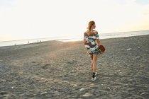 Femme tenant skateboard sur la plage — Photo de stock