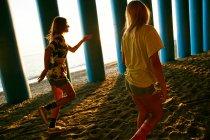 Mulheres caminhando na praia perto de colunas — Fotografia de Stock