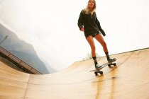 Young woman skating on ramp — Stock Photo